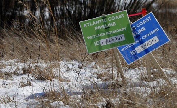 Two signs marking the Atlantic Coast Pipeline are placed in snow-covered ground.